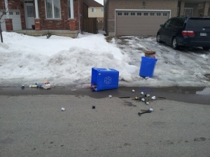 A windy day leaves recycling bins scattered on the streets.